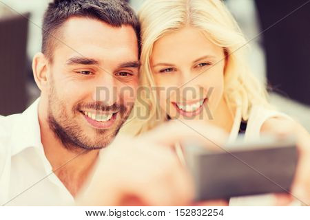 love, date, technology, people and relations concept - smiling happy couple taking selfie with smartphone outdoors