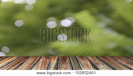 empty wooden desk with blurred abstract nature bokeh background. Outdoor view. relaxing/vacation time.