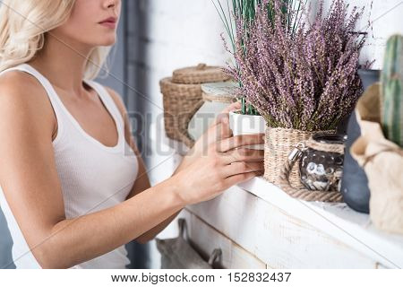 Sorting out mess. Nice blond woman standing near decorated shelf and holding white flowerpot.