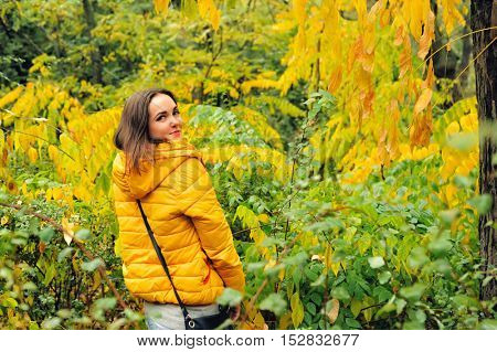 Woman in yellow hoody hiking in autumn forest.