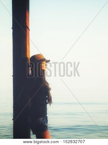 Young woman standing under the pier in a sea water, enjoy autumn sunset light and relax