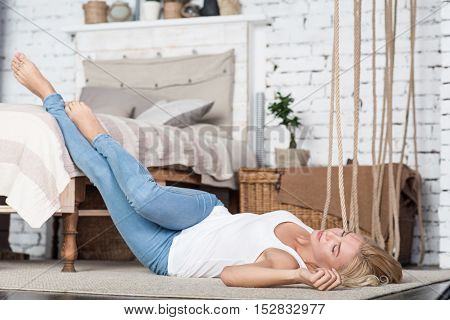 Feeling relaxation. Slim blond woman lying on floor in bedroom, holding her legs on bed.