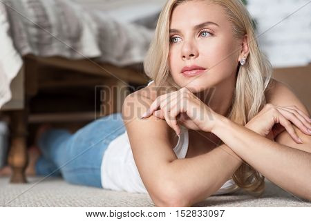 Thinking over. Close up of blond haired woman on floor in bedroom with hand at chin.