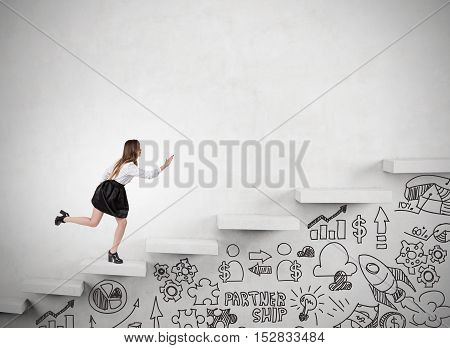Businesswoman is running up the stairs in concrete wall. Startup icons are drawn with marker under it. Concept of success in business and climbing career ladder. Mock up
