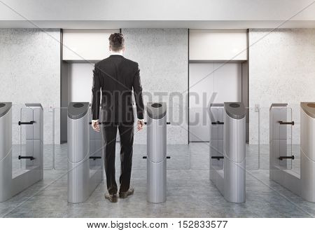Rear view of man at entrance to office with stainless steel turnstiles and two elevators. Concept of security. 3d rendering. Mockup.