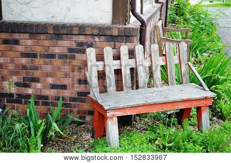 Lone wooden bench and brick wall in the side garden