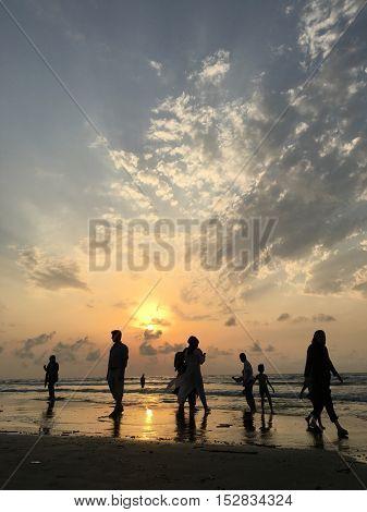 People on sea beach at sunset having fun