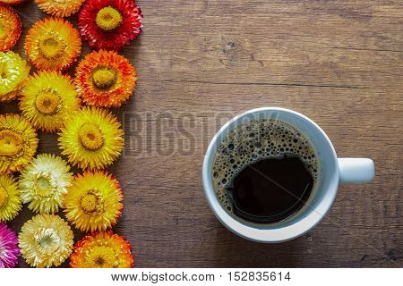 Top view of coffee cup on wooden table background with colorful straw flower