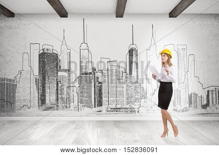 Woman in yellow hard hat is standing against city panorama drawn on concrete wall. Concept of architect's work.