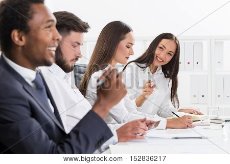 Two people flirting during a boring meeting in a white office. Concept of communication and romance.