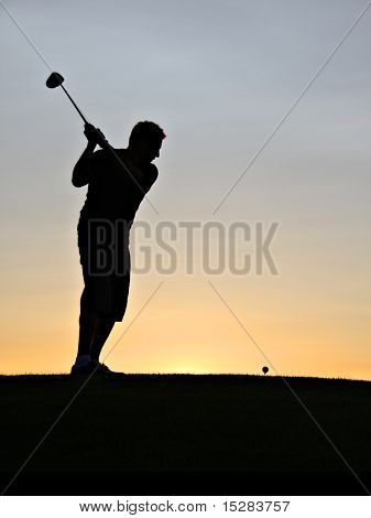 Golfer swinging his driver at sunrise.