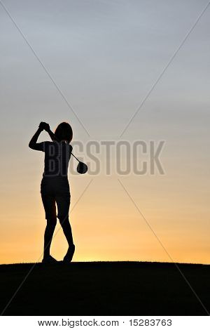 Female golfer swinging a driver at sunrise.