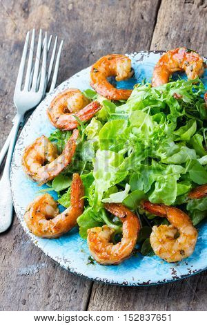 Seafood shrimp prawns. Srimp lettuce salad on blue plate with lemon rosemary arugula on wooden rustic background. Healthy food or diet concept.