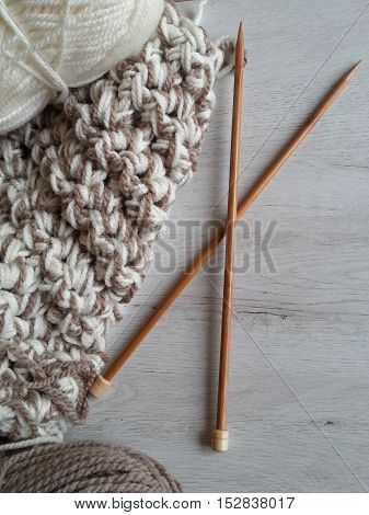 Knitted garment, wool yarn and needles for knitting on a white wooden background