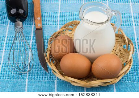 Eggs And Milk Jug In Wicker Basket, Whisk And Knife