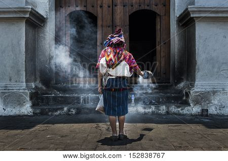 Chichicastenango Guatemala - April 26 2014: Mayan woman performing a ritual in front of the Santo Tomás church in the town of Chichicastenango in Guatemala