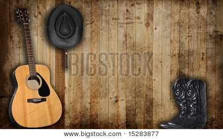 Cowboy hat, boots and guitar against an old barn background.