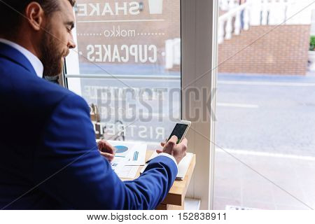 businesslike man in costume looking into his smartphone indoors
