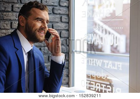 adult bearded freelancer in a suit chatting on the phone indoors with copy space