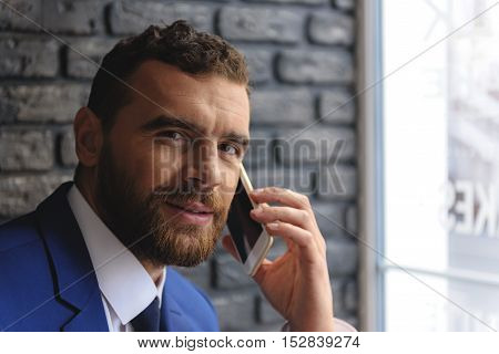 bearded manager talking on smartphone and looking into a camera indoors, close up