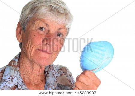 Senior lady holding a face mask for protection against the influenza virus.