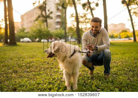 Man texting on a mobile phone while walking his dog.