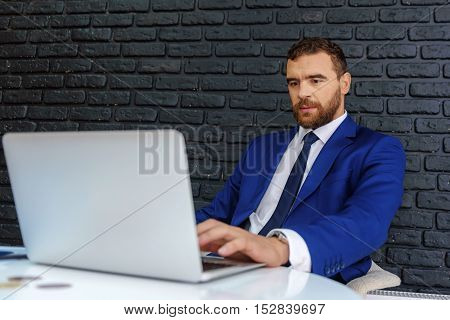 bearded guy sitting in front of laptop against black bricks with copy space