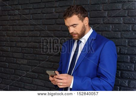 handsome businessman looking into smartphone with copy space indoors