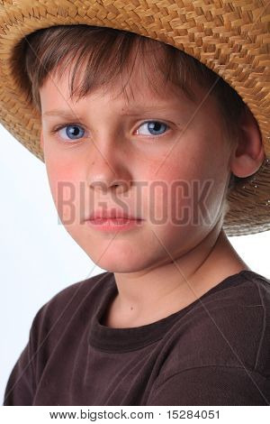 Cute freckle faced boy wearing a cowboy hat.