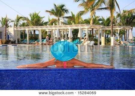 Woman wearing sun hat, relaxed in the swimming pool.