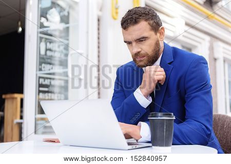 adult freelancer working on the laptop outdoors