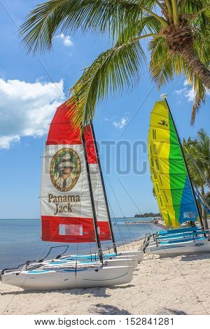 Key West, Florida, United States - April 12, 2012: colorful catamaran sailboats on shore in Smathers Beach. Smathers Beach is famous for its recreational activities.