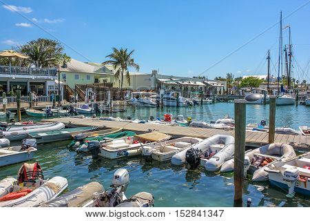 Key West, Florida, United States - April 12, 2012: boardwalk, motor and sailing boats in the small Harbor of Key West in Florida in a sunny day.
