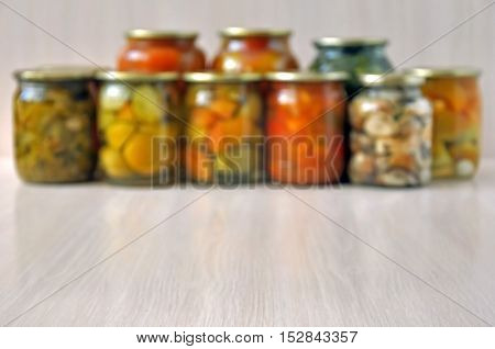 Blurred autumn background. A lot of glass jars on a wooden floor with canned pickled vegetables: tomatoes peppers mushrooms in bokeh.