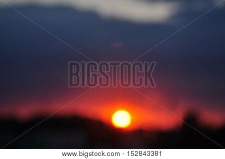 Abstract background. Blurred colorful landscape with the sky and the setting sun.