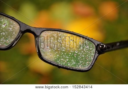Glasses in a black frame with raindrops on the lens close-up. Blurred autumn background.