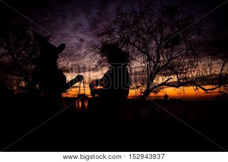 Siluet Halloween witches holding a pumpkin in sunset