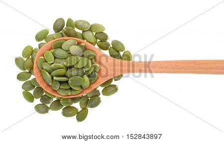 top view of pumpkin seeds in wooden spoon isolated on white