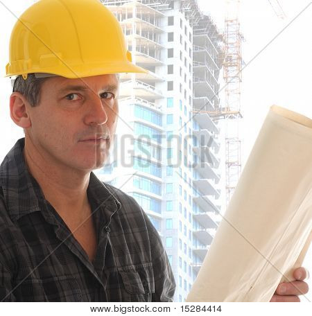 Contractor holding blue prints in front of a highrise.