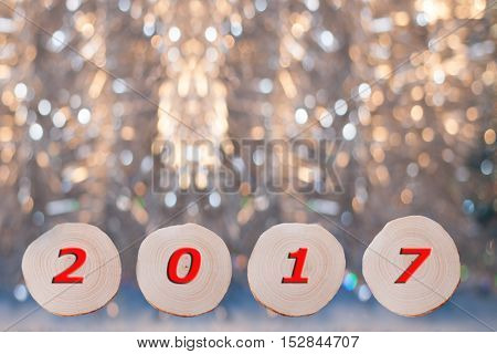 Four alder saw cuts and red date 2017 on Christmas golden bokeh background. New year or Christmas background.