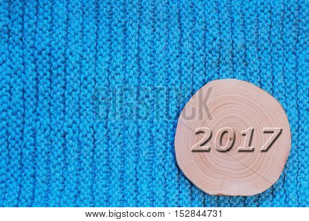Alder saw cut and convex date in 2017 against the backdrop of the blue knitted fabric. New Year`s and Christmas background.