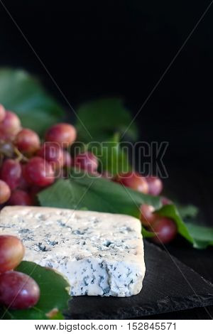 Blue cheese Dorblu with red grape on black background