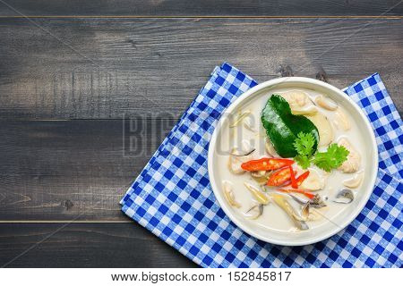 coconut milk soup with chicken or Thai chicken coconut Soup ( Tom Kha Gai ) on wooden table top view Thai local food