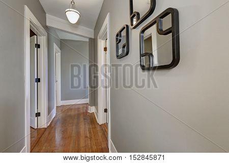 Empty Hallway Interior With Gray Walls And Hardwood Floor.
