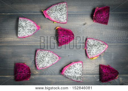 dragon fruits sliced on wooden table top view