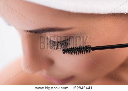 Close up of young calm woman face tightening up her artificial eyelashes by brush