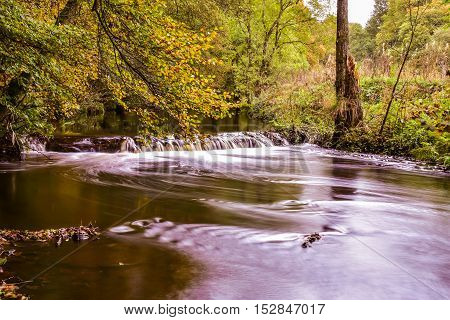 Mini waterfall in a forest in autumn on river Don In England