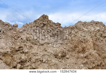 Yellow sand and gravel mountain close up on a background of blue sky.