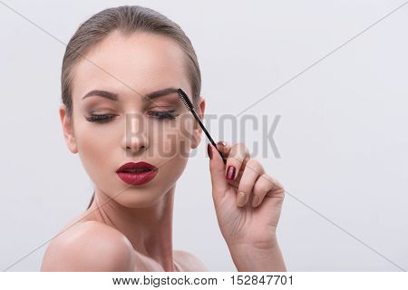 Serene young woman is touching brush to her eyebrow. She is standing with naked shoulders and looking down shyly. Isolated and copy space in right side