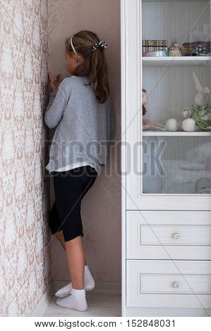 Little sad girl standing in the corner of the room
